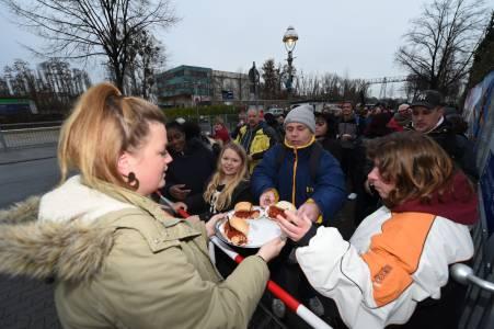 Wartende Gäste werden mit Currywurst versorgt